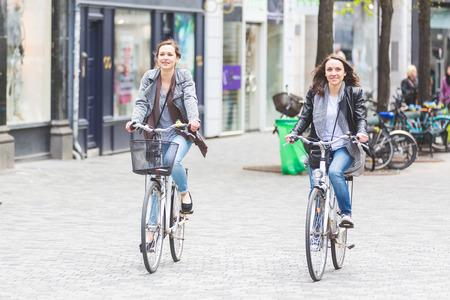 Twee vrouwen die met de fiets in Kopenhagen. Ze zijn in hun jaren twintig en ze dragen smart casual kleding. Fietsen zijn een typische wijze van vervoer in Denemarken.