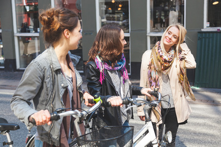 three persons only: Group of women walking in Copenhagen. They are in their twenties and they are wearing smart casual clothes. Two of them are holding a bicycle, typical mode of transport in Denmark.