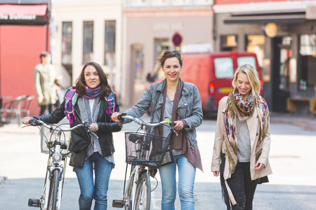 three people only: Group of women walking in Copenhagen. They are in their twenties and they are wearing smart casual clothes. Two of them are holding a bicycle, typical mode of transport in Denmark.