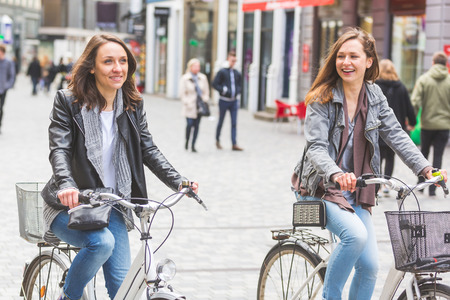three people only: Two women going by bike in Copenhagen. They are in their twenties and they are wearing smart casual clothes. Bicycles are a typical mode of transport in Denmark.