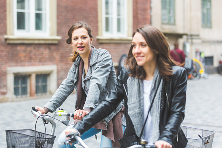 three friends: Two women going by bike in Copenhagen. They are in their twenties and they are wearing smart casual clothes. Bicycles are a typical mode of transport in Denmark.