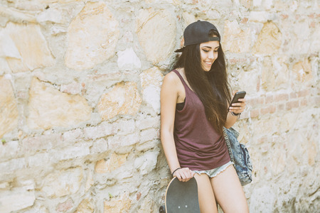 filipina: Portrait of a beautiful skater girl looking at smart phone against stone wall. She is half caucasian and half filipina, she wears short jeans, a purple tank top and a black cap.