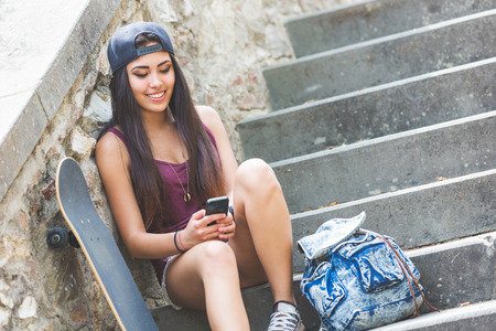 philippine adult: Portrait of a beautiful skater girl looking at smart phone at park. She is half caucasian and half filipina, she wears short jeans, a purple tank top and a black cap. Stock Photo