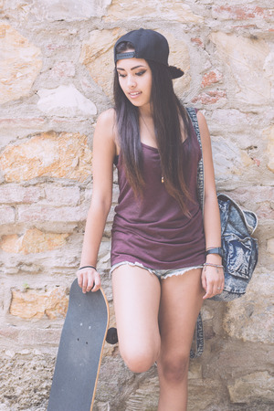 philippine adult: Portrait of a beautiful skater girl with her black skateboard against stone wall. She is half caucasian and half filipina, she wears short jeans, a purple tank top and a black cap.