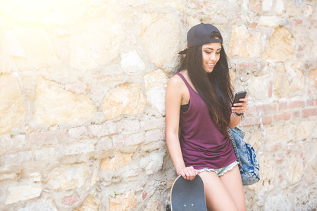 teenage girl happy: Portrait of a beautiful skater girl looking at smart phone against stone wall. She is half caucasian and half filipina, she wears short jeans, a purple tank top and a black cap.