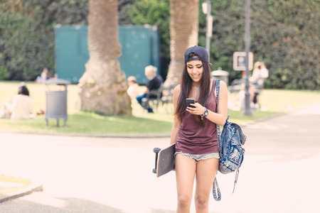 filipina: Portrait of a beautiful skater girl looking at smart phone at park. She is half caucasian and half filipina, she wears short jeans, a purple tank top and a black cap. Stock Photo