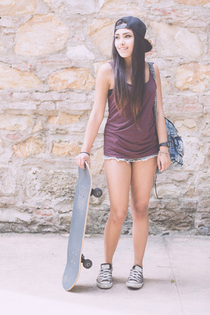 filipina: Portrait of a beautiful skater girl with her black skateboard against stone wall. She is half caucasian and half filipina, she wears short jeans, a purple tank top and a black cap.