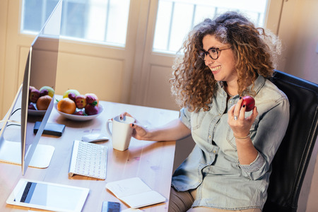 small office: Young woman working at home or in a small office, vintage hipster clothing, curly hair. She is eating some fresh fruits, there is a cup of tea or coffee on the desk with some technological devices. Stock Photo