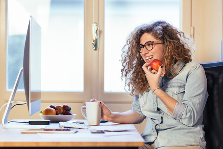 Young woman working at home or in a small office, vintage hipster clothing, curly hair. She is eating some fresh fruits, there is a cup of tea or coffee on the desk with some technological devices. Imagens