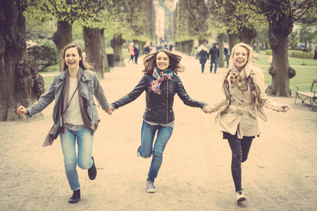 three persons only: Group of women running at park in Copenhagen. They are in their twenties and they are wearing smart casual clothes. Happiness, friendship and lifestyle concepts.