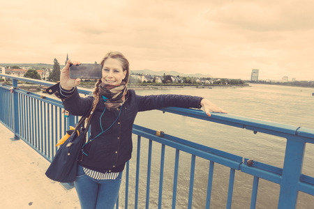 rhein: German girl taking selfie in Bonn with Rhein on background. She is standing next to the railing, holding the smart phone with one hand and looking at it.