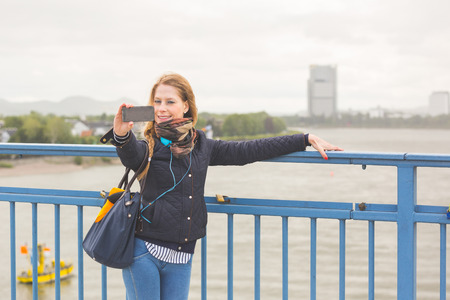 german girl: German girl taking selfie in Bonn with Rhein on background. She is standing next to the railing, holding the smart phone with one hand and looking at it.
