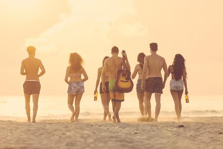 Groep vrienden wandelen op het strand bij zonsondergang. Er zijn vier meisjes en drie jongens, het zand waait, backlight techniek, achteraanzicht.