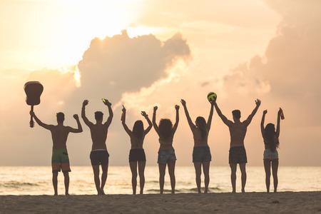 guitarra: Silueta de un grupo de amigos con las manos levantadas en la playa al atardecer. Hay cuatro niñas y tres niños, uno está sosteniendo una guitarra y otro una pelota. Técnica de luz de fondo. Foto de archivo
