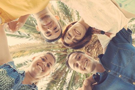 view girl: Group of teenagers embraced in circle, bottom view. They are two girls and two boys, smiling and looking down to the camera.