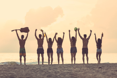 holiday party: Silhouette of a group of friends with raised hands on the beach at sunset. There are four girls and three boys, one is holding a guitar and another one a ball. Backlight technique. Stock Photo