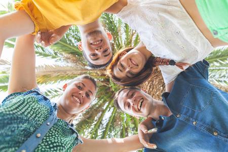 young students: Grupo de adolescentes que abrazó en círculo, vista desde abajo. Se trata de dos niñas y dos niños, sonriendo y mirando a la cámara.