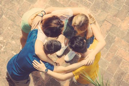 aide à la personne: Groupe d'adolescents embrassé dans le cercle, vue aérienne. Ils sont deux filles et deux garçons, à la recherche de l'autre Banque d'images