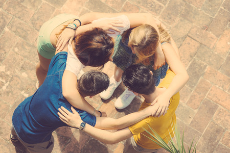 Group of teenagers embraced in circle, aerial view. They are two girls and two boys, looking each other
