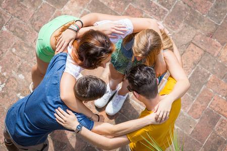 Groupe d'adolescents embrassé dans le cercle, vue aérienne. Ils sont deux filles et deux garçons, à la recherche de l'autre Banque d'images - 41886045