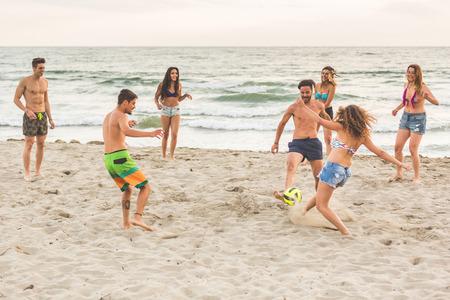 jugando futbol: Grupo multirracial de amigos que juegan con la bola en la playa. Hay cuatro niñas y tres niños, con una niña filipina y un chico español. Foto de archivo