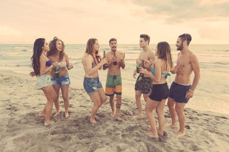 多种族小组的朋友在海滩,跳舞和喝啤酒的一个党。他们是青少年,四个女孩和三个男孩,站在海边旁边。