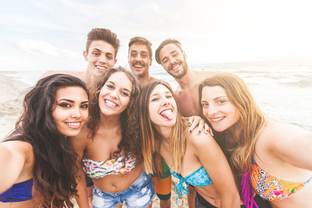 Groupe multi-ethnique d'amis prenant selfie sur le point de vue plage, caméra. Ils sont adolescents, quatre filles et trois garçons, debout juste à côté de la mer.