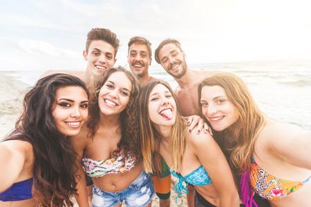 Multiraciale groep vrienden nemen selfie op het strand, camera standpunt. Ze zijn tieners, vier meisjes en drie jongens, staand net naast de zee.