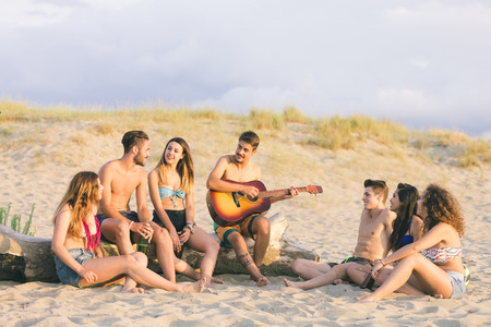playing music: Group of friends playing guitar and singing on the beach at sunset. There are four girls and three boys, some are sitting on a log, some on the sand.