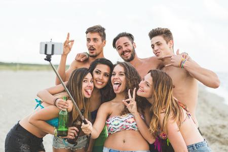 playa vacaciones: Grupo multirracial de amigos que toman selfie con un palo selfie en la playa. Son adolescentes, cuatro ni�as y tres ni�os, de pie junto a la orilla del mar.