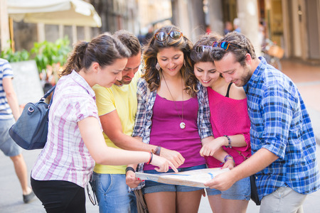 italy street: Tourists looking at city map with typical Italian street on background. The photo was taken in Pisa but could also be used for Rome, Florence or Milan.