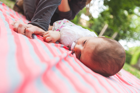 tightly: Baby daughter lying down and hugging tightly mothers finger. They are at park, the mother is smiling and cuddling her daugther.