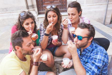 comiendo helado: Los turistas que comen aguanieve, hablando y mirando el uno al otro. La foto fue tomada en Pisa, pero tambi�n podr�a ser utilizado para Roma, Florencia o Mil�n.