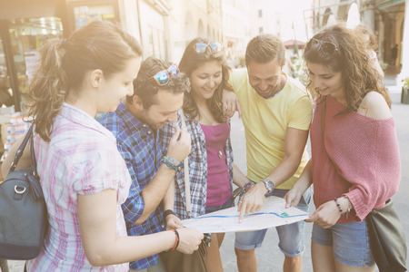 Tourists looking at city map with typical Italian street on background. The photo was taken in Pisa but could also be used for Rome, Florence or Milan. photo