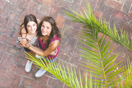 Portrait of two beautiful girls taken from above. They are embraced and looking up at camera. Lifestyle and friendship concepts.