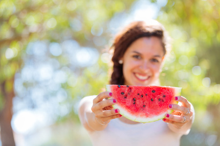 water melon: Beautiful young woman showing a slice of watermelon as a smile. She is caucasian, she wear a white dress and she has a braid on the shoulder. Summer and lifestyle concepts.