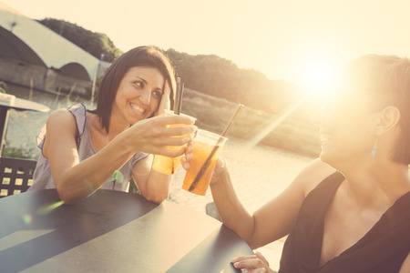 Two beautiful caucasian women having a cocktail and toasting outdoor on summer. The bar is next to a river, backlight scene at sunset. photo