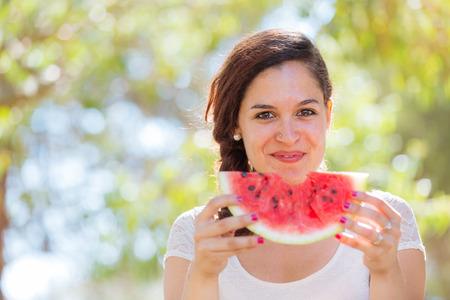 Mooie jonge vrouw bij park het eten van een stukje watermeloen. Ze is Kaukasisch, dragen ze een witte jurk en ze heeft een vlecht op de schouder. Zomer en lifestyle concepten.
