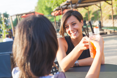 cocktail bar: Two beautiful caucasian women having a cocktail and toasting outdoor on summer. The bar is next to a river, backlight scene at sunset.