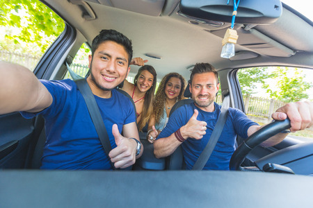 latinas: Group of friends taking a selfie into the car before leaving for vacations. They are a mixed race group of four persons, two caucasian and two hispanic.