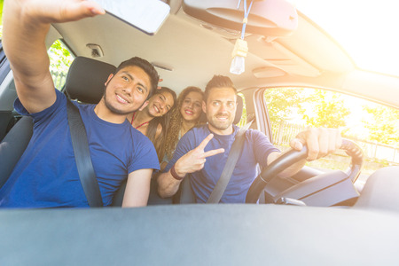 Group of friends taking a selfie into the car before leaving for vacations. They are a mixed race group of four persons, two caucasian and two hispanic.