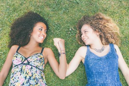 Twee mooie vrouwen liggend op het gras. Een daarvan is Kaukasisch, de andere is zwart, multicultureel en vriendschap concepten.