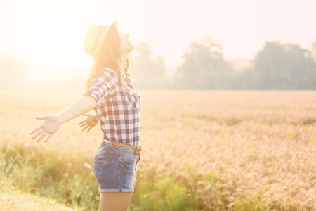 freedom: Joyful woman in the countryside with wheat field on background. She is wearing short jeans, a checked shirt and a straw hat. Freedom and happiness concepts.