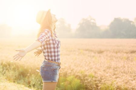 libertad: Mujer alegre en el campo con campo de trigo en el fondo. Ella lleva los pantalones vaqueros cortos y una camisa a cuadros y un sombrero de paja. Conceptos libertad y felicidad.