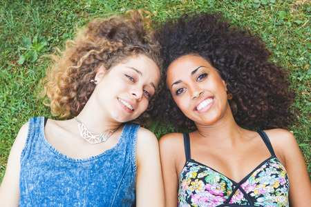 lesbianas: Una pareja multirracial de la mujer tirado en el pasto. Se trata de dos mujeres jóvenes que descansan en el parque. Una es rubia caucásica y la otra es morena negro, ambos tienen el pelo rizado. Ellos están sonriendo y vistiendo ropa de verano. Foto de archivo