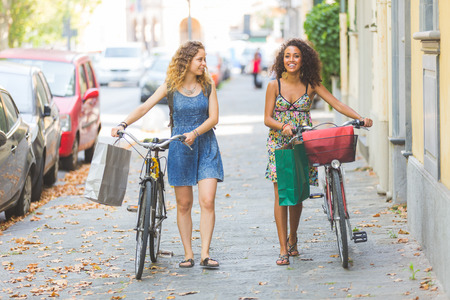 lesbian love: Multiracial couple of friends riding bikes on the street. They are two women wearing summer clothes and walking on a small street with their bikes. They are bringing some shopping bags.
