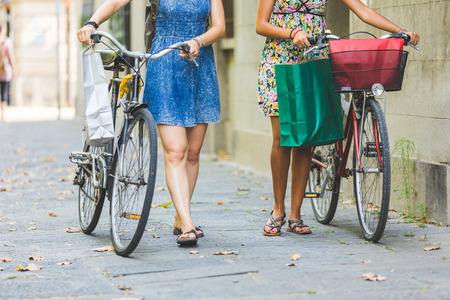 lesbians: Multiracial couple of friends riding bikes on the street. They are two women wearing summer clothes and walking on a small street with their bikes. They are bringing some shopping bags.