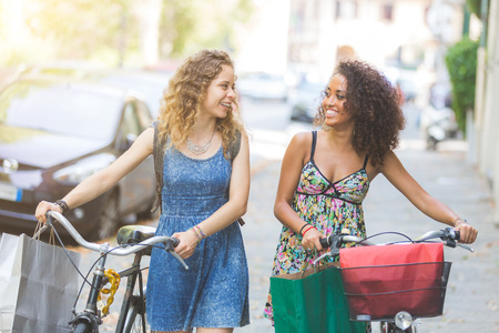 Multiracial couple of friends riding bikes on the street. They are two women wearing summer clothes and walking on a small street with their bikes. They are bringing some shopping bags.