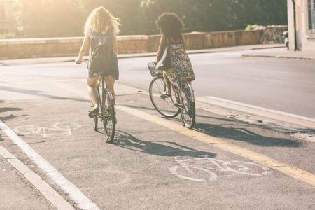 Paar van de vrouwelijke vrienden paardrijden fietsen op straat. Focus op de fiets pictogram. Het zijn twee vrouwen zomer kleding rijden fietsen. Ze staan op het fietspad langs een stad weg.
