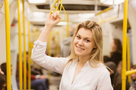 Beautiful blonde young woman holding with right hand inside tube train in London. She wears a white shirt and she is looking at camera smiling.